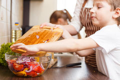Family cooking. Mum and children in the kitchen. Family cooking background. Small boy help his mother with mixing salad in the kitchen Royalty Free Stock Image