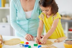 Happy mother and daughter making cookies at home. Family, cooking and people concept - happy mother and little daughter with molds making cookies from dough at royalty free stock images