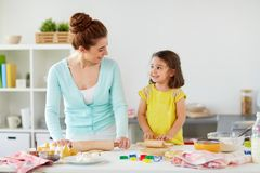 Happy mother and daughter making cookies at home. Family, cooking and people concept - happy mother and little daughter with rolling pins making cookies from royalty free stock images