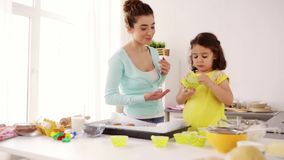 Mother and daughter cooking cupcakes at home stock footage
