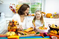 Family cooking pumpkin soup for Halloween lunch stock photo