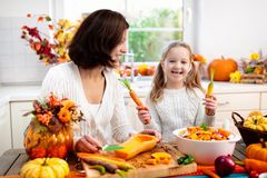 Family cooking pumpkin soup for Halloween lunch royalty free stock images
