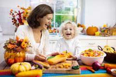 Family cooking pumpkin soup for Halloween lunch stock image
