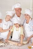 Family cooking together. An elderly couple and their grandson knead the dough for the pie together Royalty Free Stock Photos