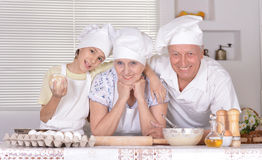 Family cooking together. An elderly couple and their grandson knead the dough for the pie together Stock Photography