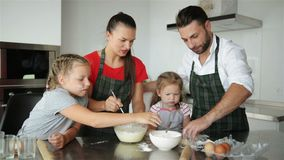 Family Cooking Together. They Have a Lot of Fun Playing On Kitchen. Cute Daughters With Their Handsome Parents Playing stock footage