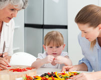 Family cooking together in the kitchen Stock Images