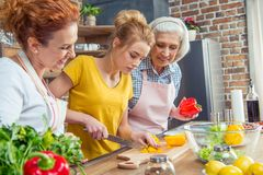 Happy three-generation family cooking together vegetable salad stock photo