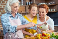 Happy three-generation family cooking vegetable salad together. In kitchen stock image