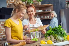 Happy family cooking together vegetable salad. In kitchen stock image