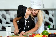 A family of cooks.Healthy eating.Mother and son prepares vegetable salad in kitchen. stock images