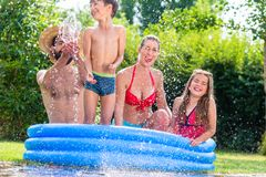 Family cooling down splashing water in garden pool. Family in garden pool splashing water cooling down, mother, father and kids having fun together royalty free stock images