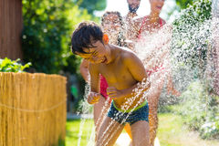 Family cooling down with sprinkler in garden Stock Photography