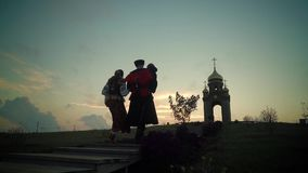 Family Cossacks in historical clothes went up the hill to the chapel. On sunset stock footage