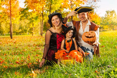 Family in costumes sit on grass with pumpkin Stock Photo