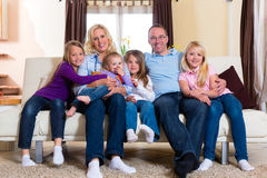Family on a couch. Family, father, mother and four sisters sitting on a couch in their living room stock photography