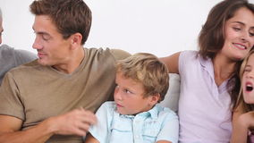 Family on couch chatting happily Royalty Free Stock Image