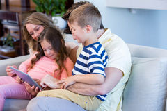 Family on the couch together using tablet pc Stock Photography