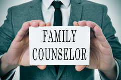 Family counselor. A man wearing a suit sitting in a desk with a desktop nameplate in front of him with the word family counselor stock photography