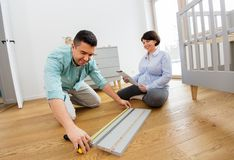 Family couple assembling baby bed at home. Parenthood, family and nursery concept - happy middle-aged men and his pregnant wife user manual and ruler assembling stock photos