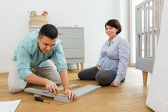 Family couple assembling baby bed at home. Pregnancy, family and nursery concept - happy middle-aged men with his pregnant wife assembling and measuring baby bed royalty free stock photography