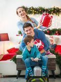 Family couple with a boy with gifts are having fun playing at home in Christmas decorations. Family couple with a boy with gifts are having fun playing at home royalty free stock image