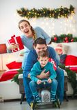 Family with boy having fun playing at home in Christmas decor. Family couple with a boy with gifts are having fun playing at home in the Christmas decorations stock photo