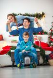 Family with boy having fun playing at home in Christmas decor. Family couple with a boy with gifts are having fun playing at home in the Christmas decorations royalty free stock image