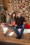 Family couple at christmas tree with gifts. Young married couple at christmas tree with gifts, portrait in a beautiful festive interior Royalty Free Stock Photography