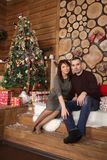 Family couple at christmas tree with gifts. Young married couple at christmas tree with gifts, portrait in a beautiful festive interior Royalty Free Stock Photo