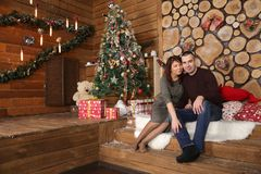 family couple at christmas tree with gifts royalty free stock photo