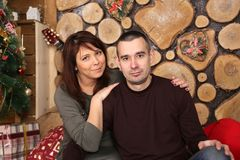 Family couple at christmas tree with gifts. Young married couple at christmas tree with gifts, portrait in a beautiful festive interior Stock Images