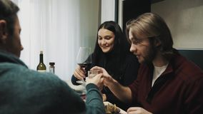 Family couple clings glasses and drinks while talking to friend at dinner table stock video