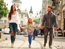 Family couple with daughter walking the street of tourist city. Young family couple with daughter walking the street of the old tourist city Royalty Free Stock Image