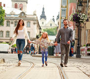Family couple with daughter walking the street of tourist city. Young family couple with daughter walking the street of the old tourist city Royalty Free Stock Photography