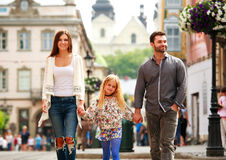 Family couple with daughter walking the street of tourist city. Young family couple with daughter walking the street of the old tourist city Stock Image