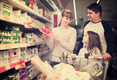 Family couple and girl choosing sweet pudding and smiling stock image