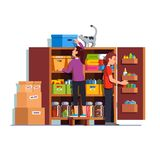Man and woman working at home pantry or cellar. Family couple man, woman working together putting boxes to home pantry or cellar cupboard shelves. Storage room Royalty Free Stock Image