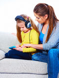 Family couple, mother and daughter play with tablet PC. Sofa Royalty Free Stock Image