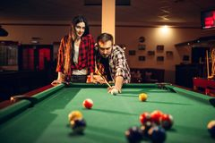 Family couple plays in billiard room. Man and women leisures, american pool game in sport bar, male player aiming to shot stock photo