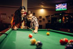 Family couple plays in billiard room. Man and women leisures, american pool game in sport bar, male player aiming to shot stock photography