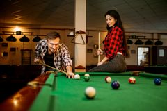 Couple plays in billiard room, male player aiming. Family couple plays in billiard room. Man and women leisures, american pool game, male player aiming to shot stock photo