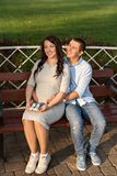 Family couple pregnant woman and a man sitting and hugging on bench in park and holds sneakers for newborn royalty free stock photo