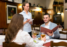Family couple in restaurant. Young family couple eating out in a tavern. Man is holding a menu in his hands while his girlfriend is taking a sip from a glass of Royalty Free Stock Photography