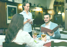 Family couple in restaurant. Young family couple eating out in a tavern. Man is holding a menu in his hands while his girlfriend is taking a sip from a glass of Stock Image