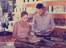 Family couple selecting erotic video in shop indoors Royalty Free Stock Image