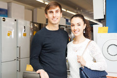 Family couple selecting new domestic appliances. Middle class family couple selecting new domestic appliances at hypermarket royalty free stock photo