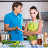 Family couple with serious faces quarrelling in kitchen Stock Photography
