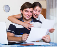 Family couple sitting at desk with documents indoors Stock Image