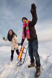 Family couple with sleigh on hill Stock Photo